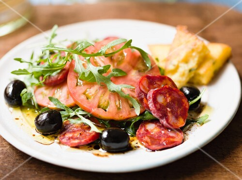 A salad of tomatoes with chorizo, olives, rocket and polenta triangles