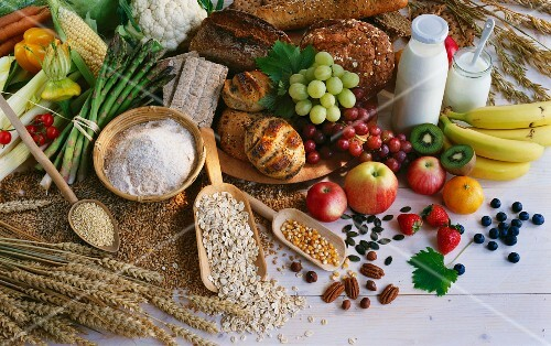 A still life of cereals, bread, vegetables, fruit, nuts and milk