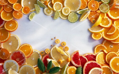 Sliced citrus fruits arranged around the edge of the image