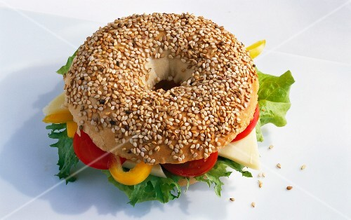 A sesame seed bagel filled with vegetables and cheese