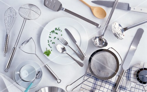 Assorted kitchen utensils, cutlery, a plate, a cup, a kitchen timer and a tea towel
