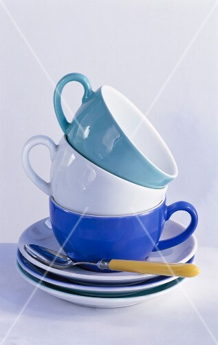 A stack of cups with saucers and a spoon