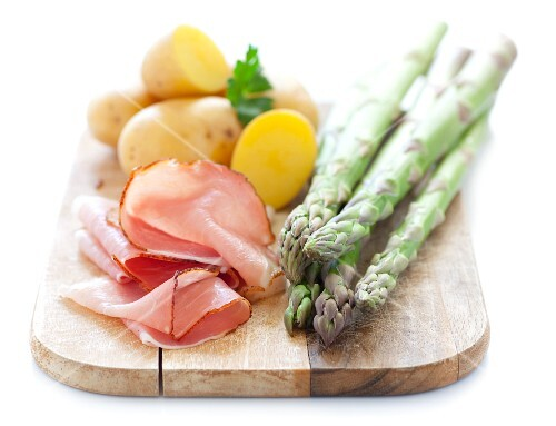 Green asparagus, ham and potatoes on a chopping board