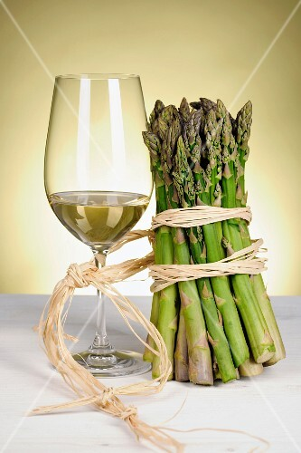 Glass of white wine and green asparagus tied together