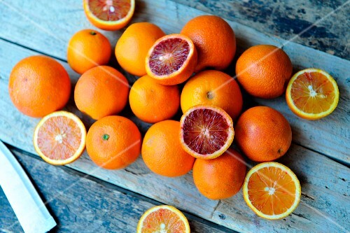 A still life of whole and halved oranges