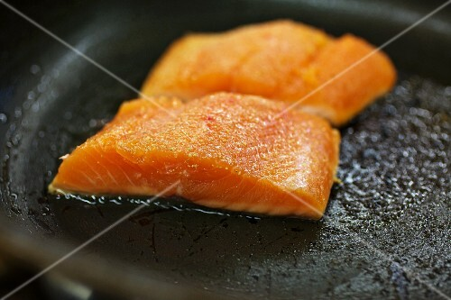 Salmon trout being fried in a pan