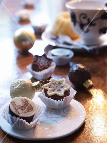 An ornate plate of chocolate treats in paper cases, on a golden table covering
