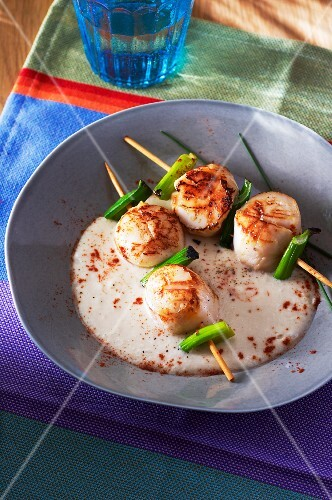 Skewers of scallops in a foaming wine sauce