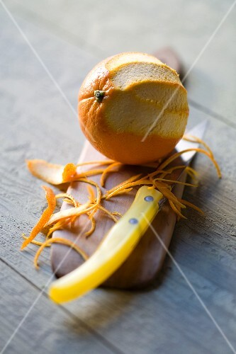 An orange and strips of orange zest