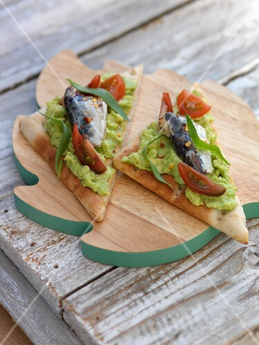 Bread triangles topped with avocado purée, tomatoes and sardines