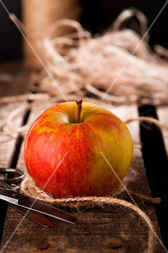An apple with string and scissors