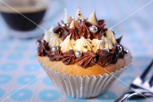 A cupcake with piped cream icing and silver balls