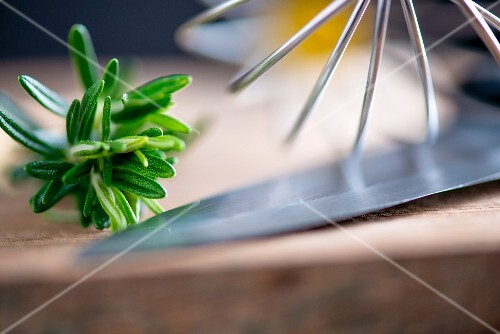 Rosemary, an egg whisk and a knife (close-up)
