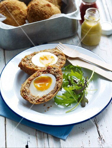 A Scotch egg with salad leaves