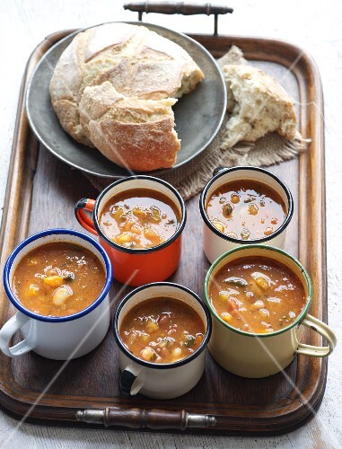 Several mugs of soup and white bread on a wooden tray