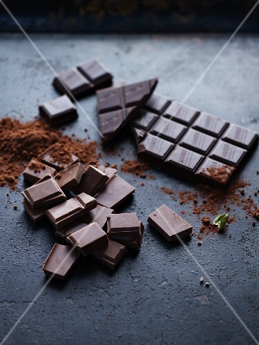 Pieces of chocolate, a bar of chocolate and cocoa powder