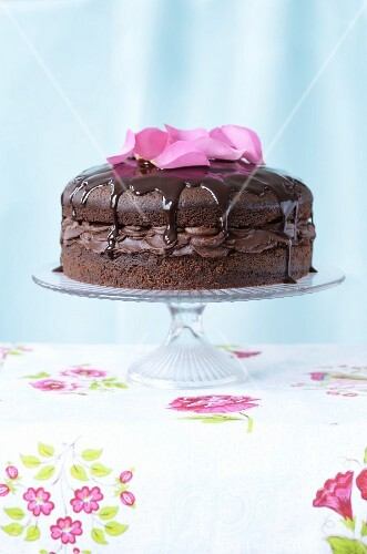 A chocolate layer cake topped with rose petals, on a cake stand