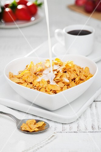 Milk being poured into a heart-shaped bowl of cornflakes