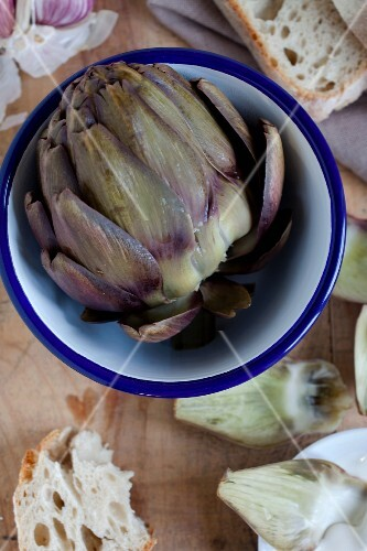 A cooked artichoke in a bowl with bread (view from above)