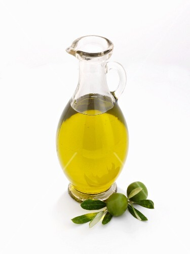 A glass carafe of olive oil against a white background