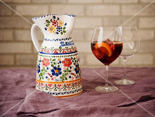A Sangria Pitcher with a Floral Design with a Glass of Sangria; Empty Glass