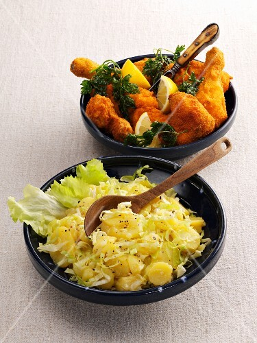Potato and endive salad served with breaded chicken pieces