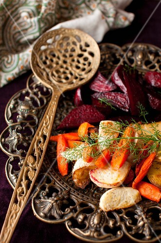Roasted Root Vegetables with Fennel Fronds on a Platter with a Spoon