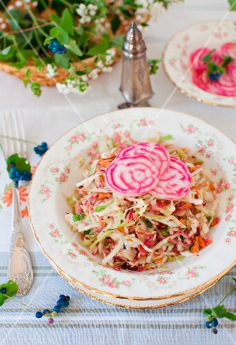 Cabbage Salad Topped with Sliced Variegated Beets; On a Table with a Basket of Flowers