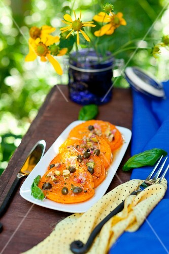 Pan Fried Yellow Tomatoes with Pistachio Caper Relish; On a Platter on an Outdoor Table