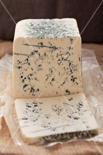 Blue cheese, partly slices, on paper