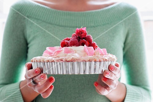 A Woman Holding a Pavlova Topped with Raspberries
