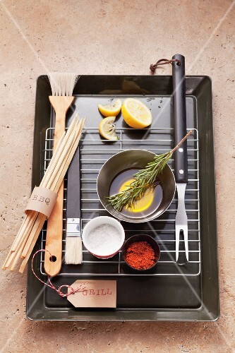 Assorted barbecue utensils, seasonings, lemons and olive oil on a barbecue grill