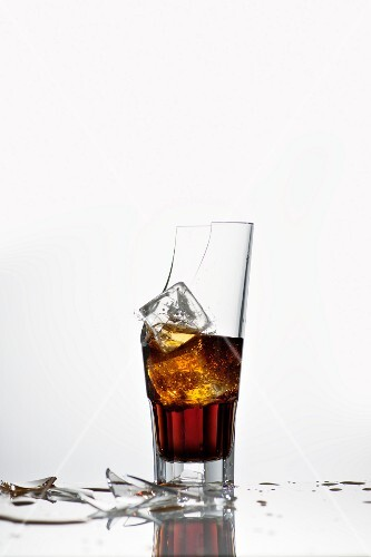 A broken glass with cola and ice cubes