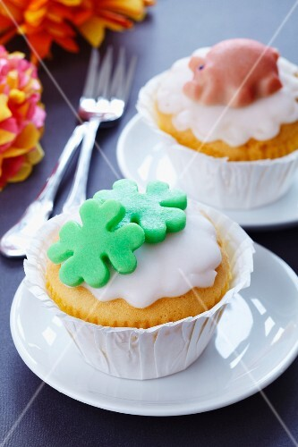 Muffins decorated with marzipan clover leaves and lucky pigs