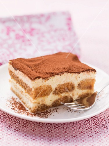 A piece of tiramisu on a plate with a fork
