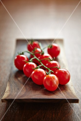 Cocktail tomatoes lying on a shallow wooden plate