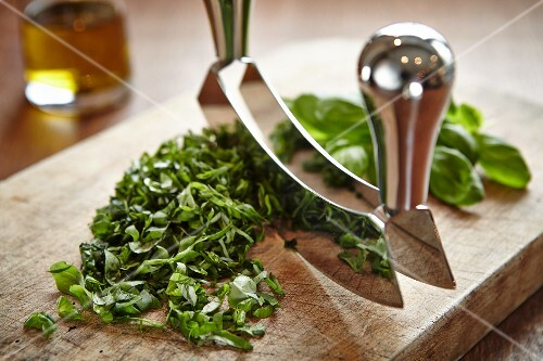 Basil being chopped with a curved chopping knife on a wooden board