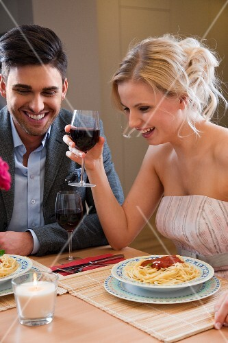 A young couple drinking red wine with spaghetti and tomato sauce in a restaurant