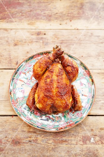 A whole roast chicken on a ceramic dish