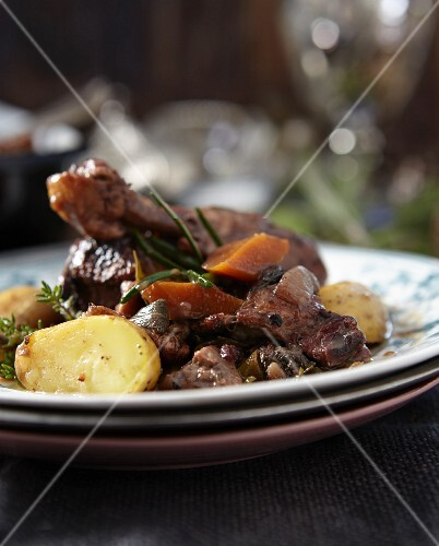 Coq au vin on stacked plates