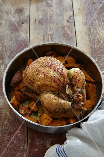 A whole roast chicken with yams