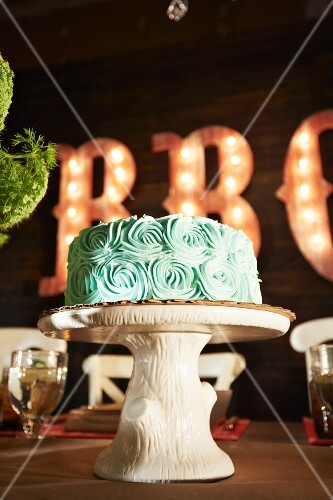 Chocolate Cake with Green Icing on a Faux Wood Cake Stand; On a Table in a Barbecue Restaurant