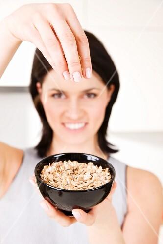 A woman holding up a bowl of porridge oats