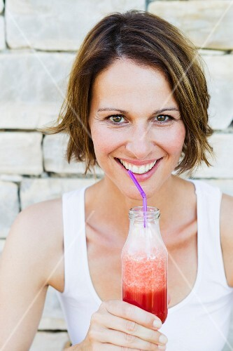 A smiling woman drinking a smoothie from a bottle