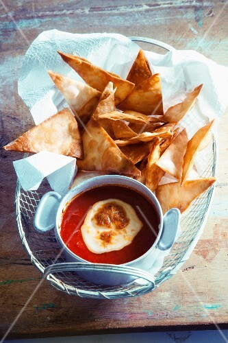 A tomato dip with cheese and tortilla chips