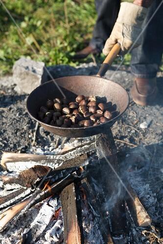 Maroni am offenen Feuer in einer Eisenpfanne rösten