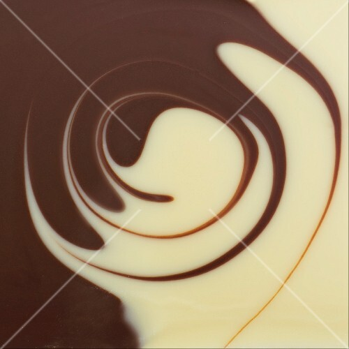 The surface of white and dark chocolate sauces, partly spiralled together