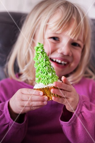 A young girl holding a Christmas tree cupcake in both hands