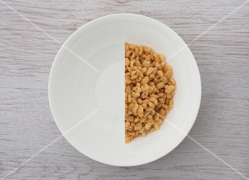 A halved portion of cereal in a white bowl (view from above)