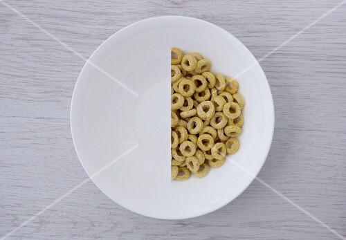 A halved portion of cereal hoops in a white bowl (view from above)